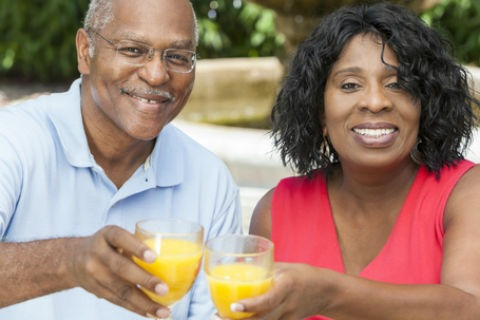 A couple toasting with orange juice. Having difficulty swallowing affects quality of life.