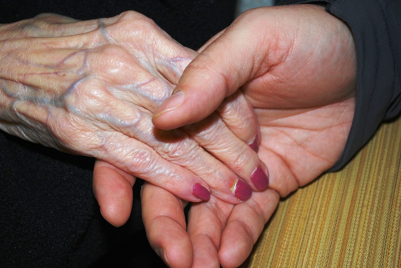 Young therapist holding hands with an elderly woman. Patient safety and compassion!